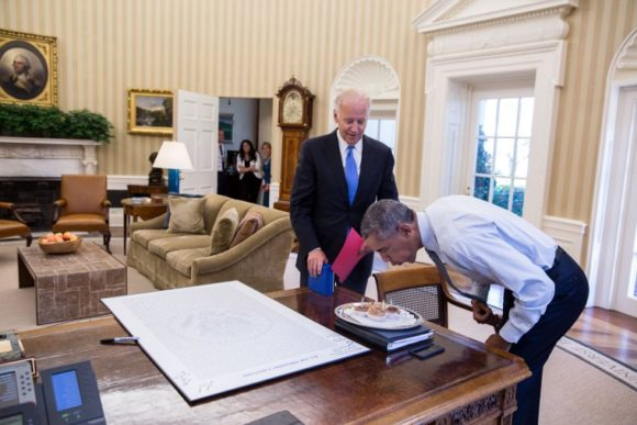 President Barack Obama blows out candles on birthday cupcakes brought to him by Vice President Joe Biden in the Oval Office, Aug. 4, 2016. (Official White House Photo by Pete Souza) This official White House photograph is being made available only for publication by news organizations and/or for personal use printing by the subject(s) of the photograph. The photograph may not be manipulated in any way and may not be used in commercial or political materials, advertisements, emails, products, promotions that in any way suggests approval or endorsement of the President, the First Family, or the White House.