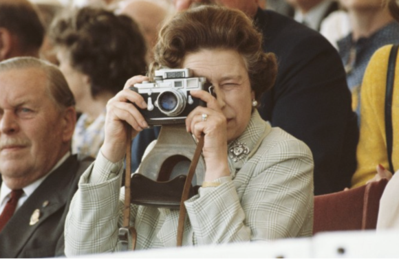 The Queen takes a picture of her husband during a horse show, May 16,1982
